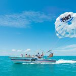 Fury small boat sailing the ocean with guests seated inside. The boat is pulling a parasail with a Fury logo on it and two guests harnessed to it.