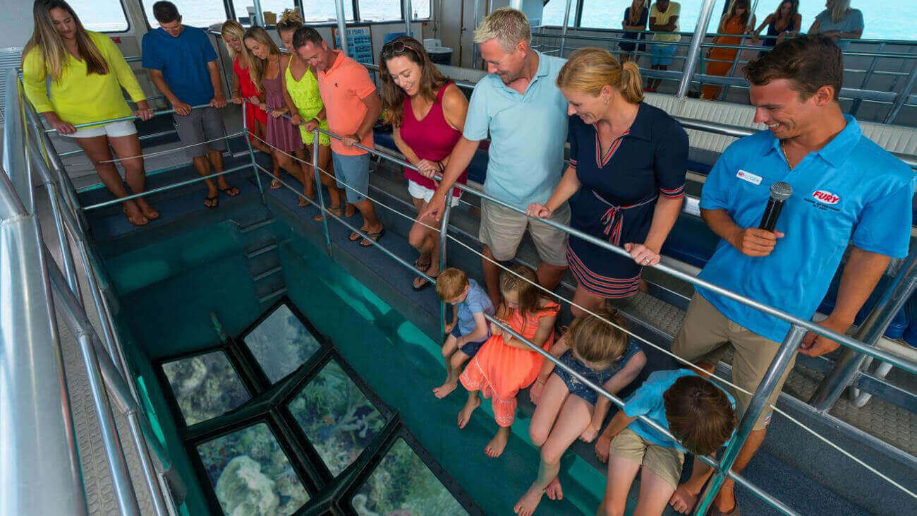 View from inside a Fury catamaran glass bottom boat showing adults and a Fury guide standing and looking down at the glass-bottom, four kids sitting with their feet dangling and also looking at the glass-bottom where they can see the ocean reef, and in the background, more adults standing and looking down at the other glass-bottom.