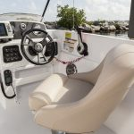 Picture of small speed boat captain chair, wheel and console and rocks and water in the background