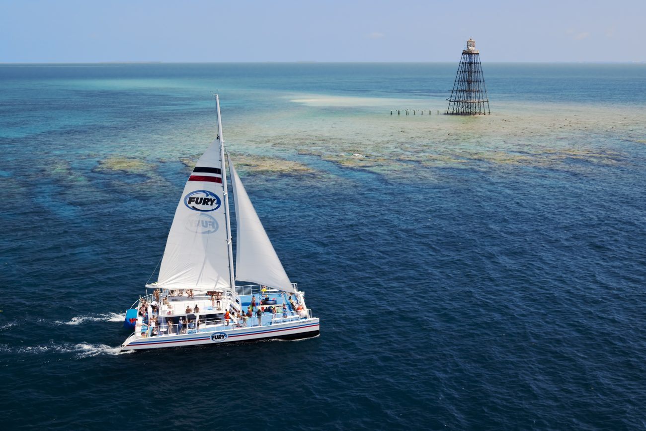 Aerial view of a Fury catamaran sailing the ocean on the lower left corner of picture. The catamaran is carrying many guests standing on decks. The background features the reef and a tower.