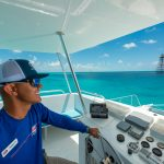 Picture of a Fury captain smiling while wearing a hat and sunglasses and standing at the helm and console inside a Fury catamaran while navigating the ocean
