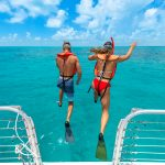 Picture of a couple wearing snorkel gear and jumping into the ocean from a catamaran deck featuring a metal railing on either side of the couple; in the background is a vast ocean and a small tower in the distance