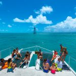 Picture of the back of a Fury catamaran deck with twelve guests wearing bathing suits while seated and chatting while a couple dressed in bathing suits is standing and also chatting; in the background is the ocean and a tower