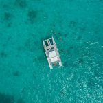 Aerial view of the ocean and a Fury catamaran with guests snorkeling the waters