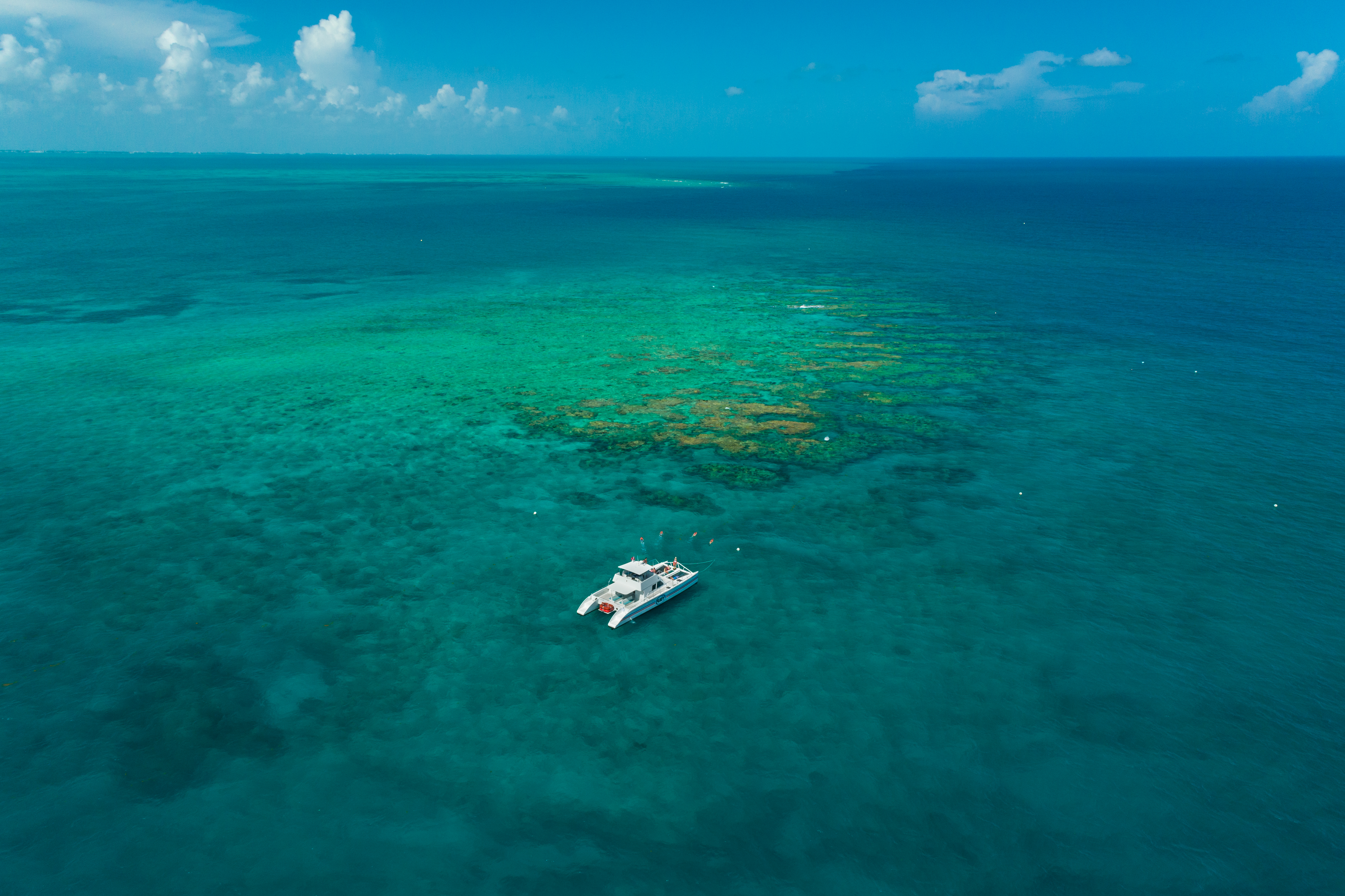Expansive aerial view of the ocean, reef, a Fury catamaran and guests snorkeling the waters