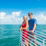 Young couple standing on a Fury catamaran deck with the ocean around them