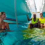 a view of the bottom of a Fury catamaran with a couple in snorkel gear sitting on the stairs ready to go in the water and a Fury female instructor in the water smiling at them