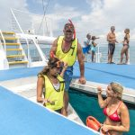 A look at a Fury catamaran deck with two couples staring at water in the background and in the foreground, a couple wearing snorkel gear going down the stairs towards the ocean while receiving instructions from a female Fury lifeguard