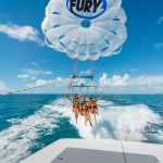Three women wearing life jackets and harnessed to a parasail that has a Fury logo on it. They are smiling and waving as the parasail takes its initial lift off. In the foreground is the back of a boat with a Fury logo and in the background is the ocean.