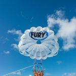 Three women wearing life jackets and harnessed to a parasail that has a Fury logo on it. They are smiling and waving as the parasail is up in the air.In the background is mostly skies and clouds and a bit of the ocean at the bottom.