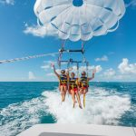 Three women wearing life jackets and harnessed to a parasail that has a Fury logo on it. They are smiling and waving as the parasail takes its initial lift off. In the foreground is the back of a boat and in the background is the ocean.