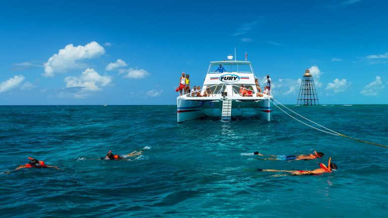 key west snorkeling with four snorkelers in the water a boat with people in the background
