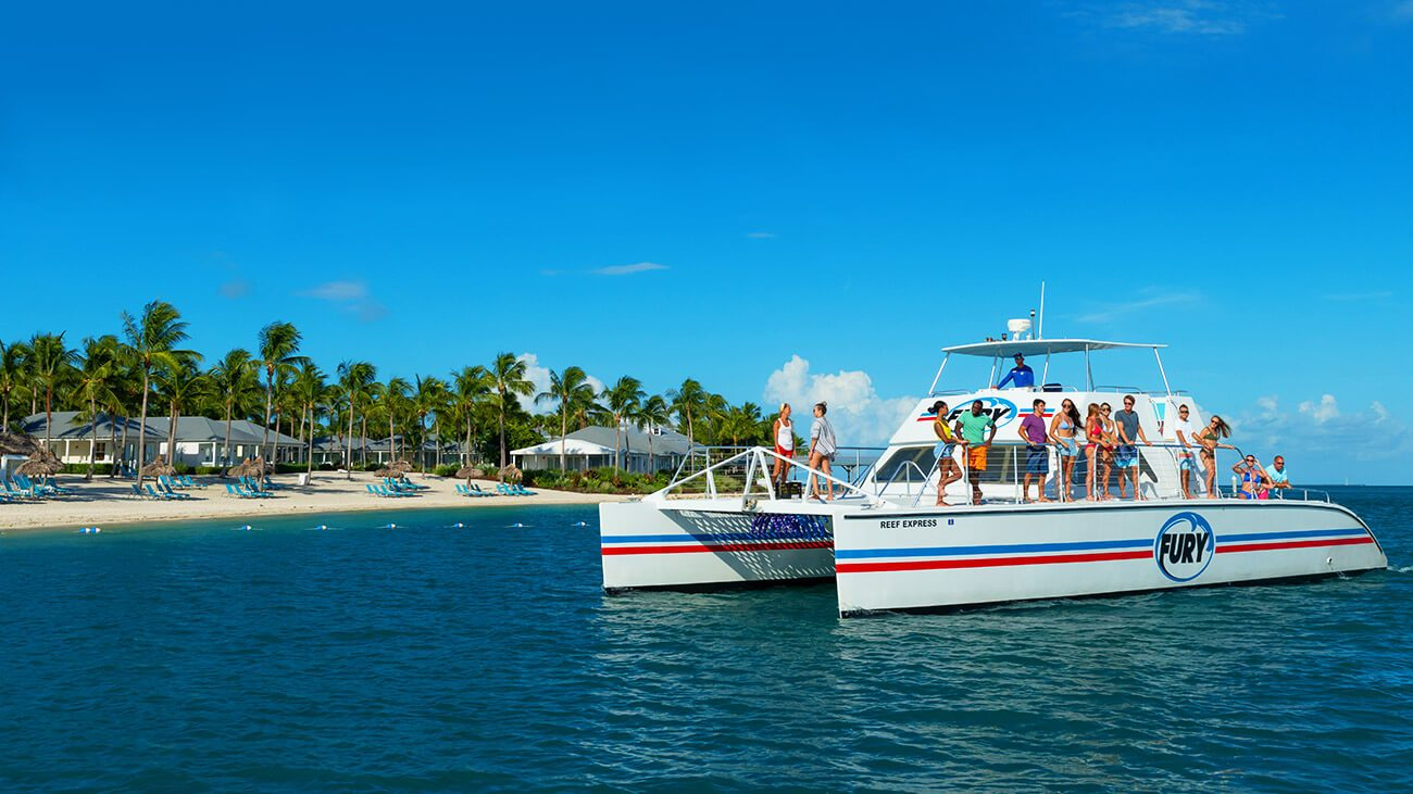 reef express catamaran on the water with the island and beach in the background