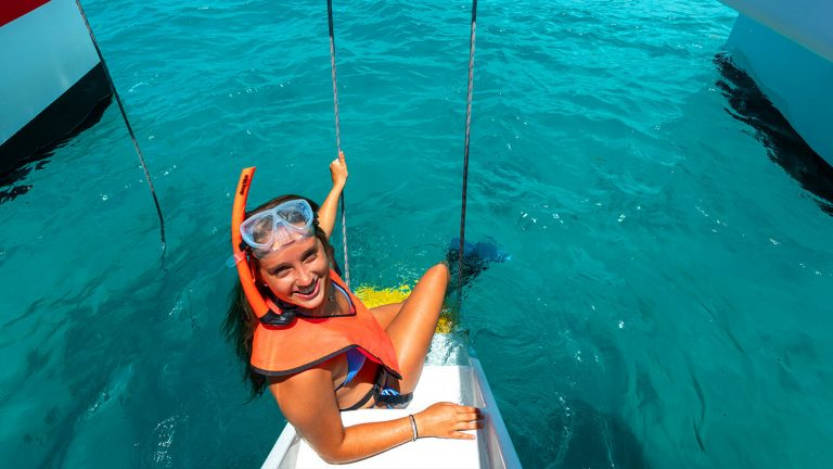 girl sitting on the stairway to the sea wearing snorkel gear on the reef express catamaran