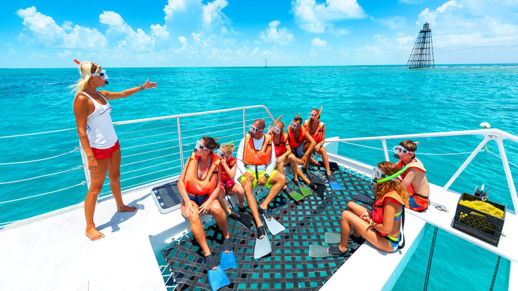 a group getting snorkel instructions from a fury employee in the front of the boat