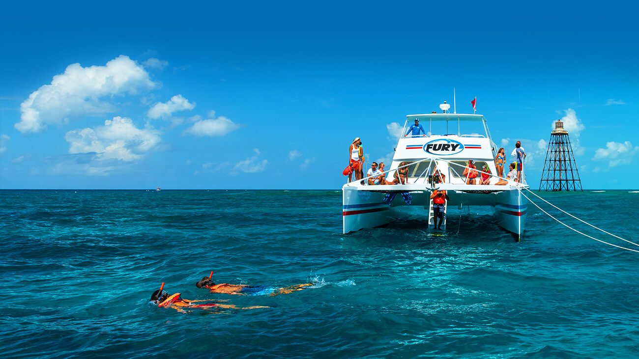 two snorkelers in the water in front of fury reef express catamaran