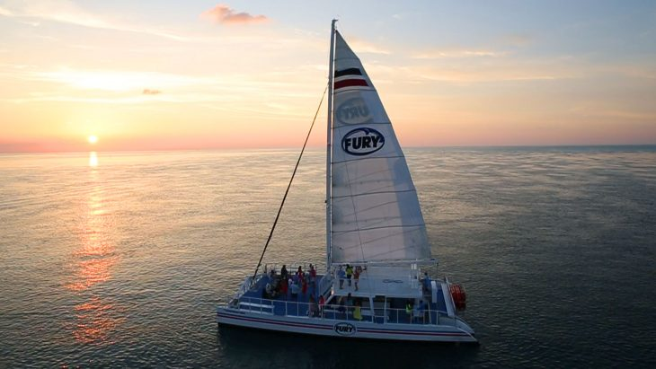 Aerial view of Fury Catamaran sailing the ocean and carrying guests with Key West sunrise on the horizon