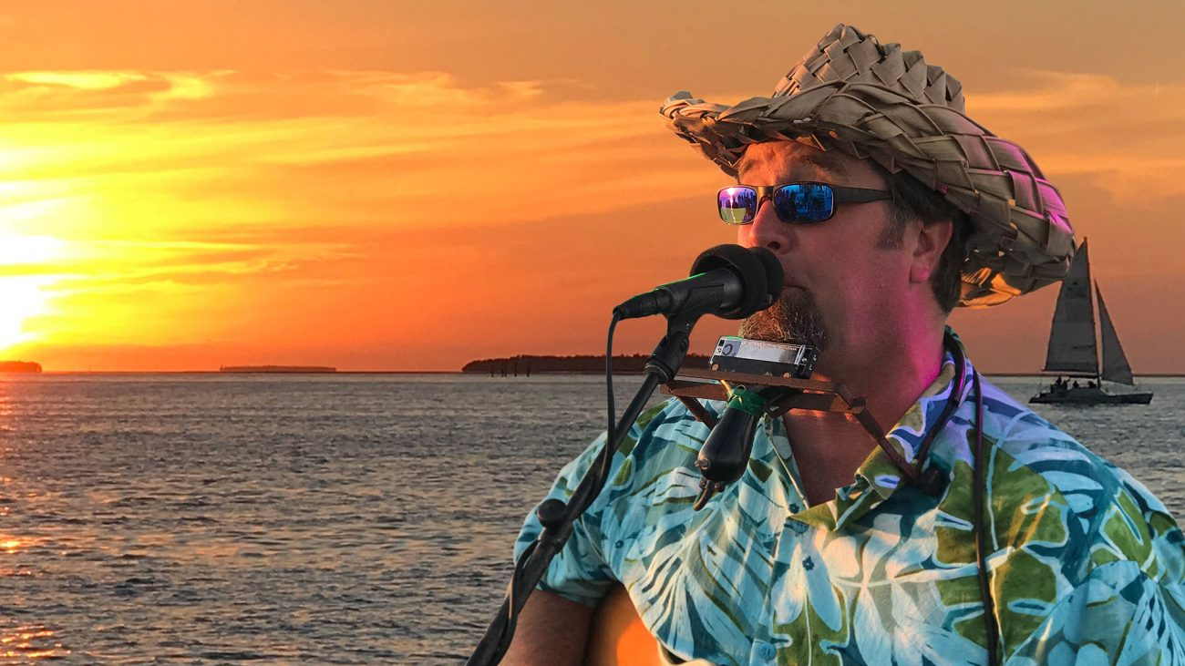 Cory Heydon wearing a straw hat and sunglasses, standing in front of a microphone and wearing a harmonica with a device holding it that wraps around his neck. He is performing Live On Fury Key West Sunset Cruise with the ocean and sunset behind him. There is also a sail boat behind him.