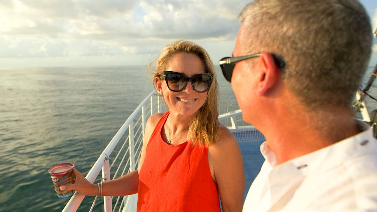 Couple wearing sun glasses and looking at each other aboard Fury's Commotion on the Ocean Sunset Cruise. Both are standing next to the railing. Woman is holding a drink. And all around them is the ocean.