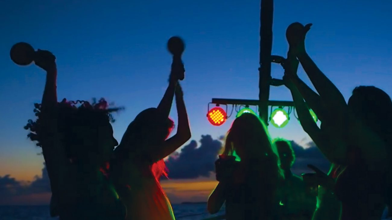 Guests dancing at night aboard Fury's Commotion on the Ocean sunset cruise with strobe lights and the ocean behind them.