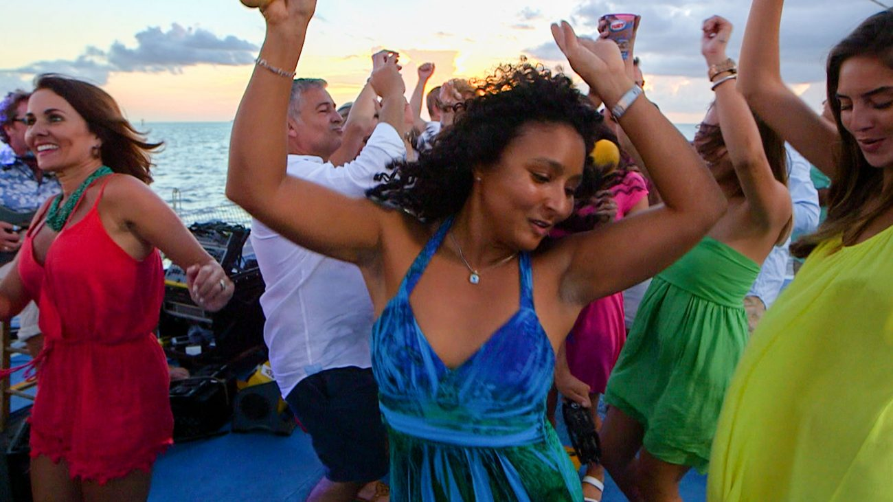 Guests dancing on Fury's Commotion on the Ocean trip with the ocean behind them.
