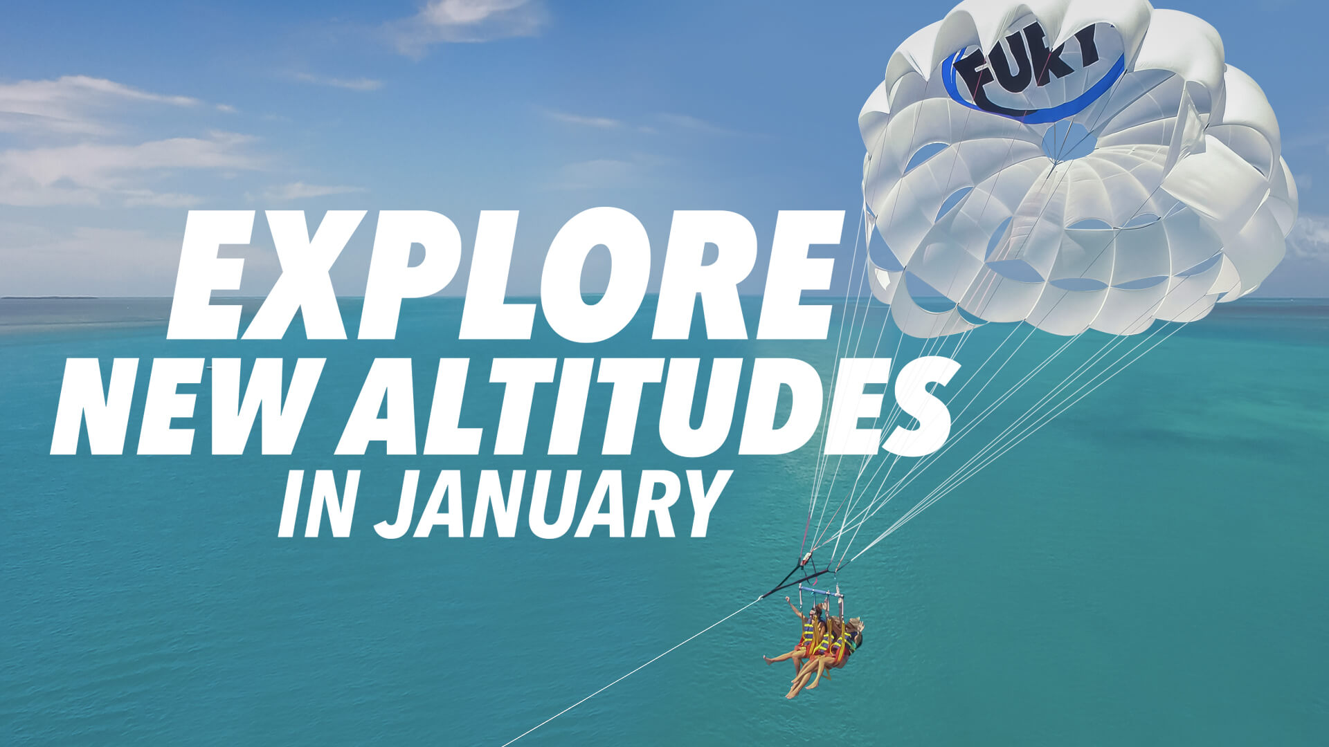 Picture of three girls flying on a Fury parasail with the ocean below them and the words 'Change Your Altitude this January'