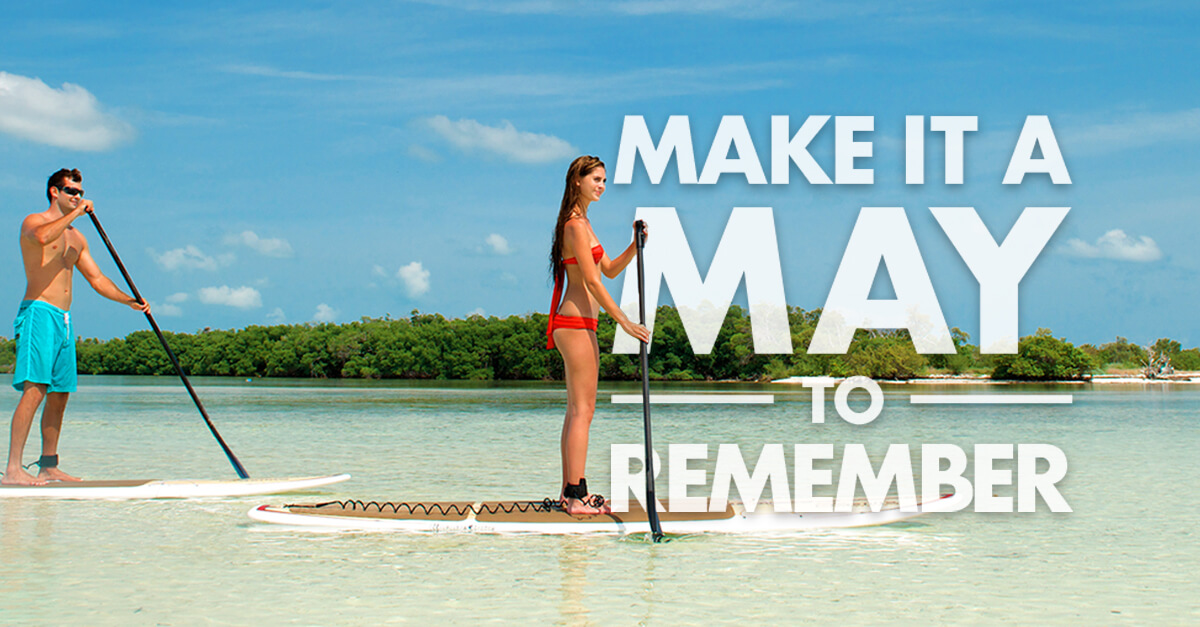 Picture of a young man and woman each standing on paddle boards on shallow ocean waters. In the background is the ocean and an island made up of trees. In the foreground to the right are the words 'MAKE IT A MAY TO REMEMBER'.