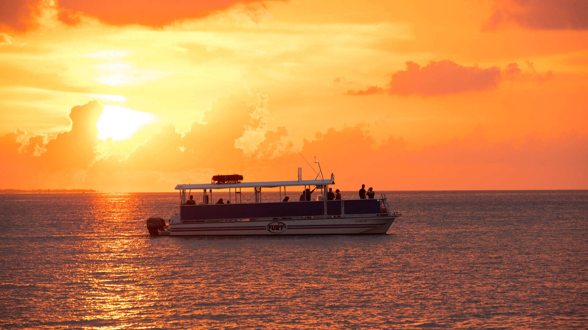orange key west sunset with a sunset cruise boat