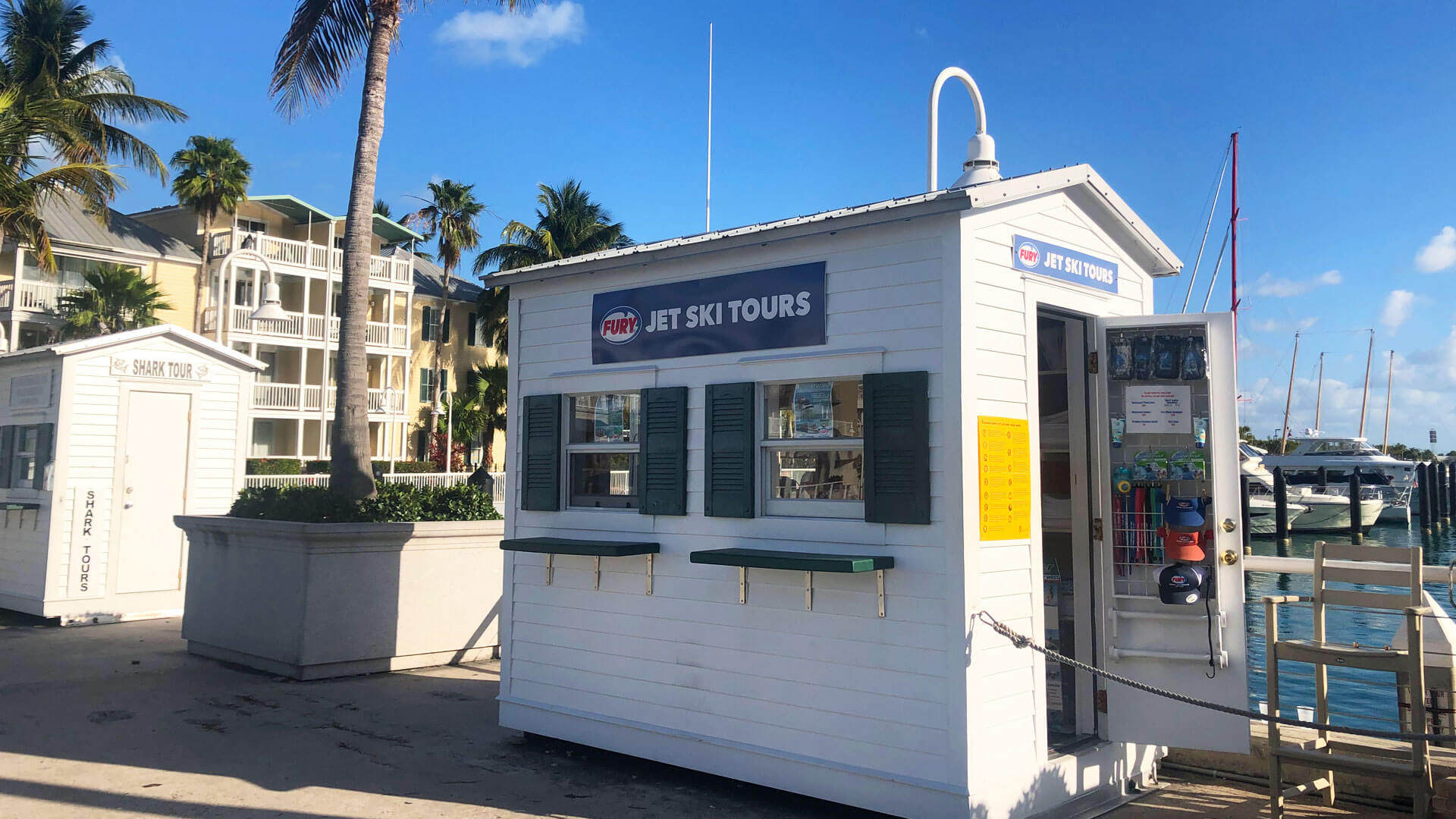 Picture of check-in booth with a sign at the top that has a Fury logo and the words 'JET SKI TOURS'. Underneath the sign are two windows with shutters and counters underneath. To the right, the booth has an open door where hats and other supples are hanging. To the left of the booth is a hotel with balconies. To the right of the booth and behind it is a marina.