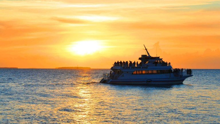 Tourists aboard Fury's glass bottom boat with sunset in background