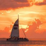 Fury catamaran with guests sailing the ocean with the sunset behind it.