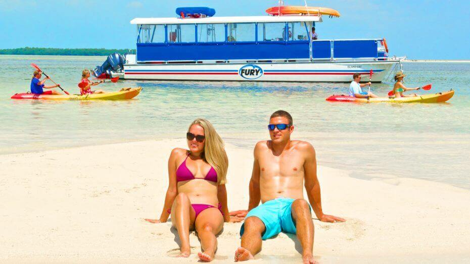 Image of couple relaxing on the sand during the Fury Island Adventure Tour