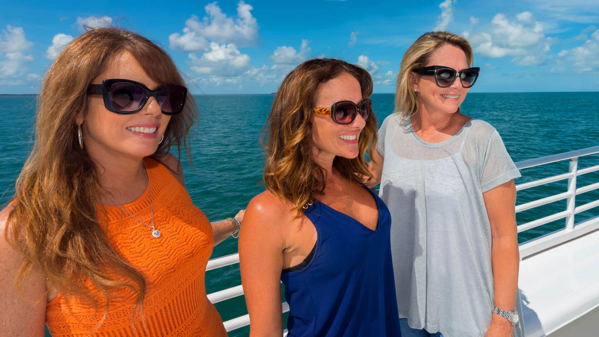 Girl friends posing for a photo aboard Fury's catamaran in Key West
