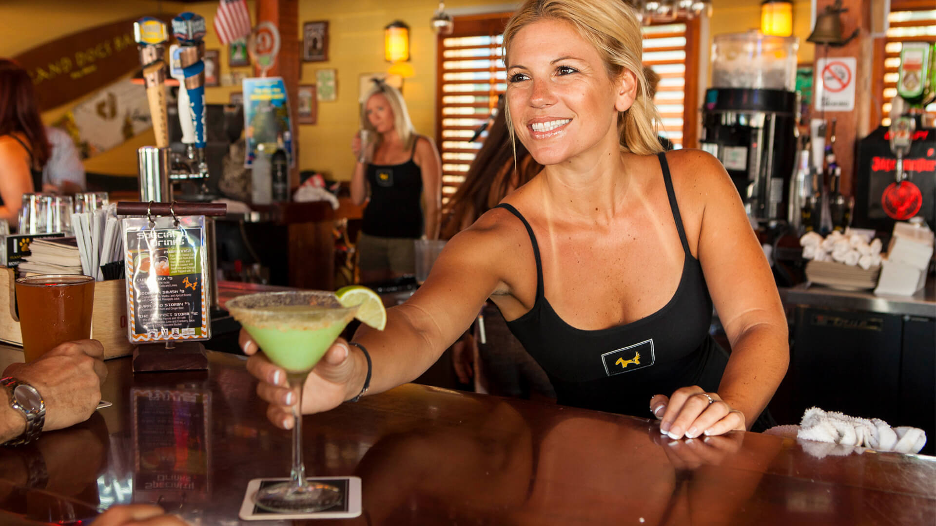 Island Dogs bartender serving a cocktail to guest