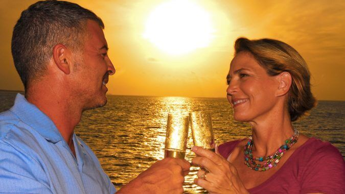 Image of couple having champagne on sunset cruise