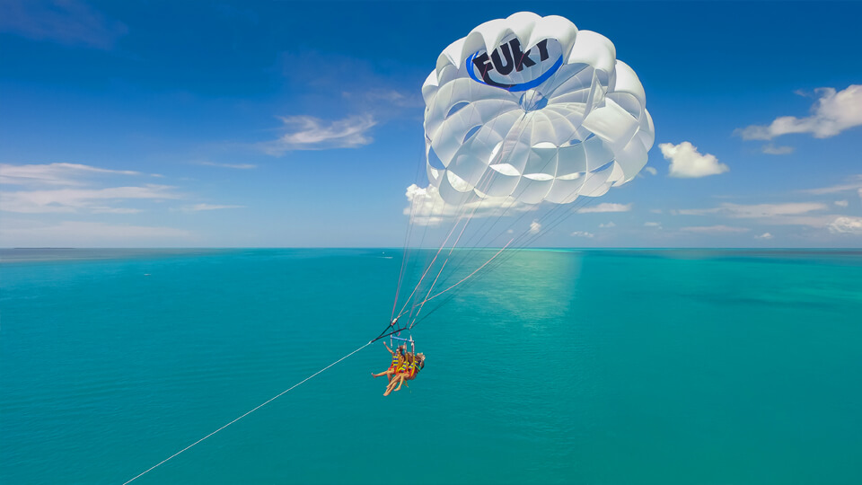 Image of couple parasailing with scenic ocean view outdoors