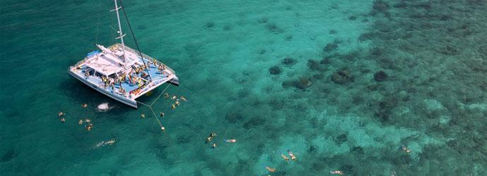 People snorkeling around a catamaran