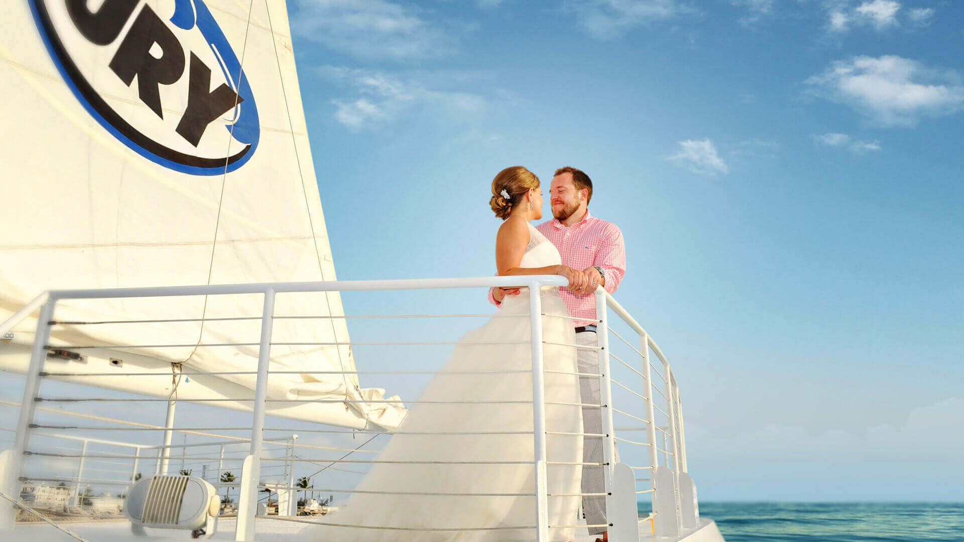 Picture of a Fury catamaran with a wedding couple looking at and smiling at each other and the ocean behind them.