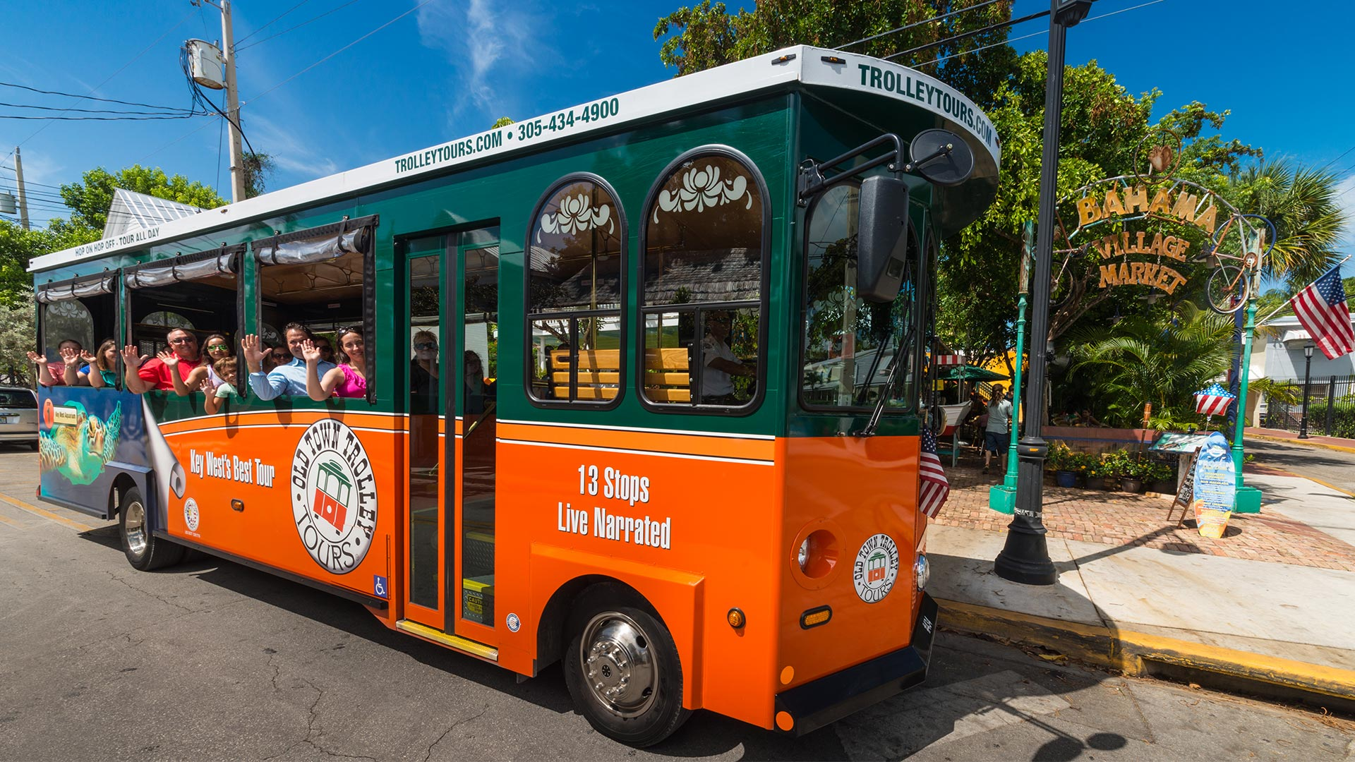 Old Town Trolley driving through Key West carrying guests who are waving at the camera