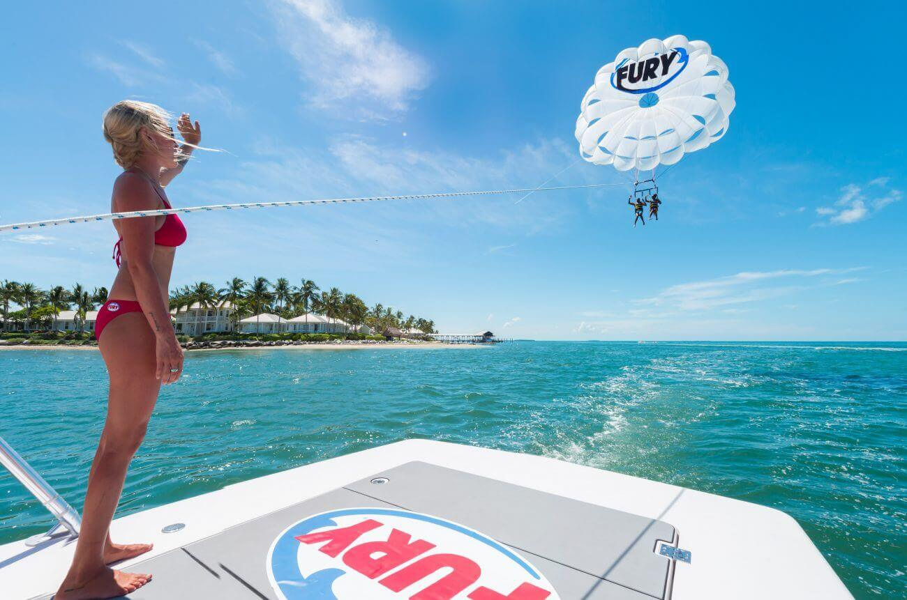 Picture of a Fury crew member wearing a bikini, standing on the back of a boat with a Fury logo on it, and looking up into the distance at two guests on a parasail waving back at her. The parasail has a Fury logo on it. In the background is the ocean and to the left is an island with homes and palm trees