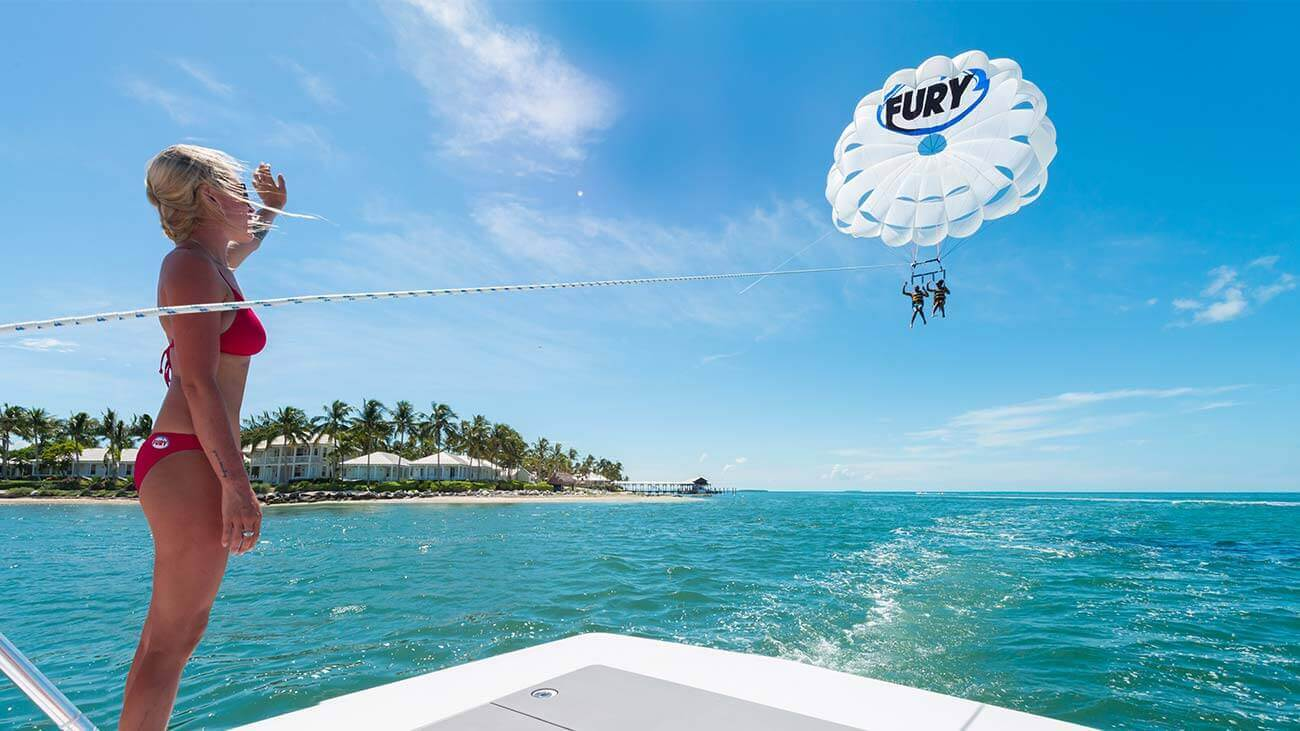 A Fury member waves at a couple parasailing in Key West