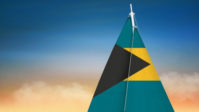sail with bahamas flag with a sunset in the background
