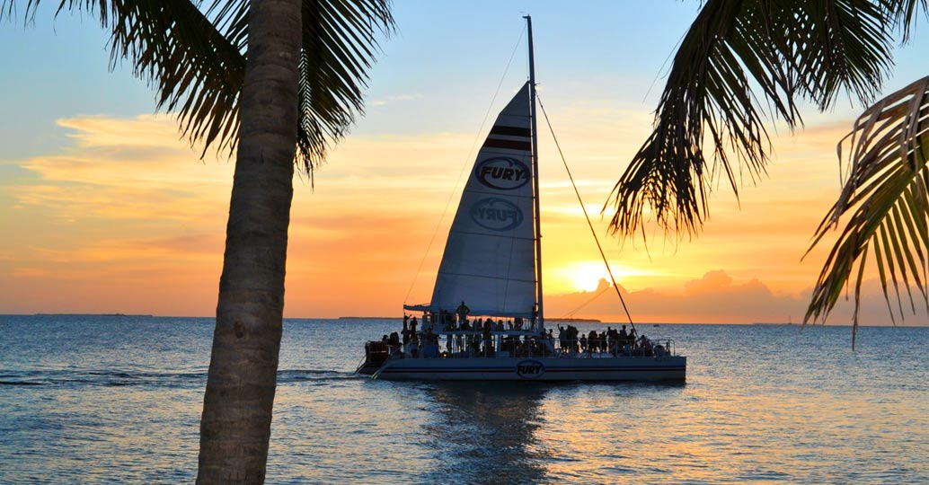 Fury Sail boat passing through some palm trees with the sunset in the background