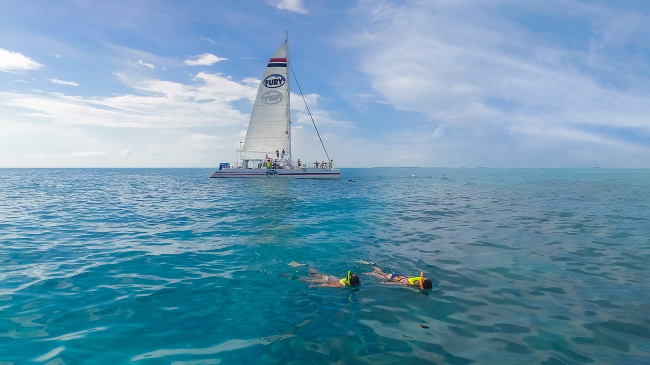 Couple of tourists snorkeling by a fury sail boat in Key West