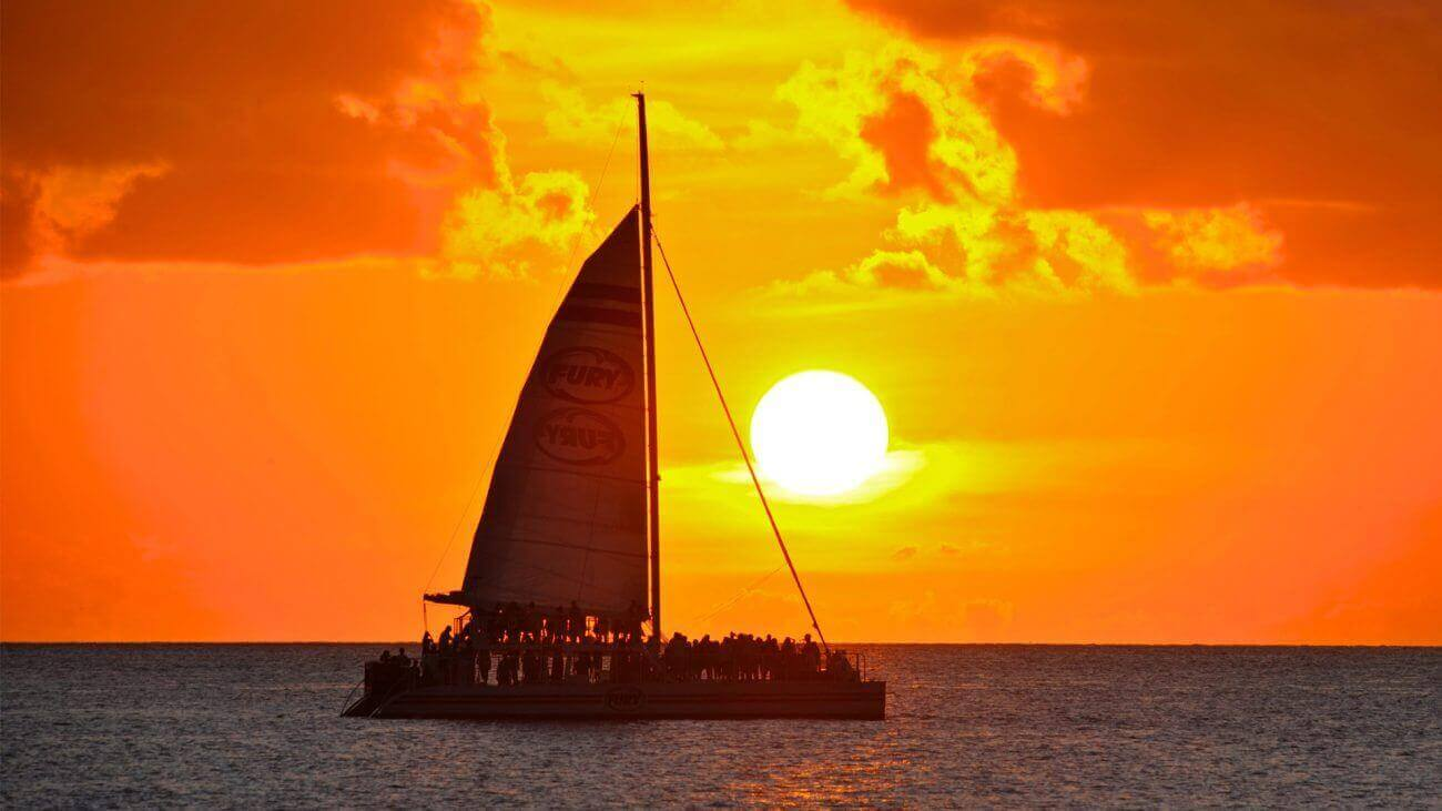 Catamaran sailing on the horizon with Key West sunset in the distance