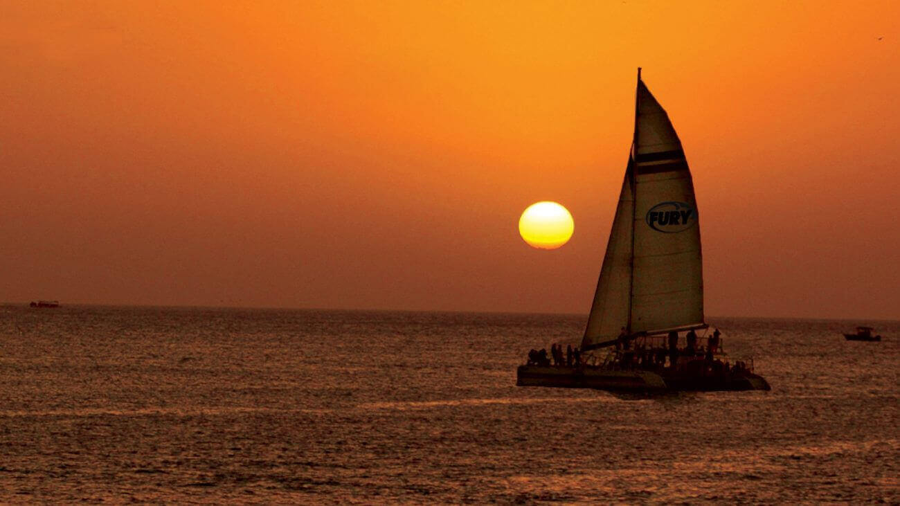 Image of a Fury catamaran on the water with Key West sunset