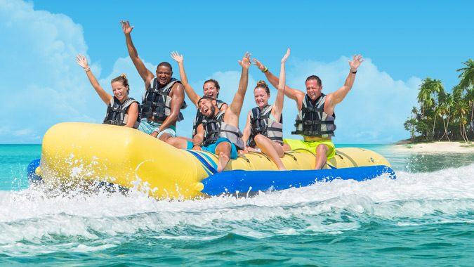 Six guests smiling, wearing life vests, raising their hands and sitting on a banana boat out the ocean. There are waves around inflatable boat and behind them to the right, is part of an island with palm trees.